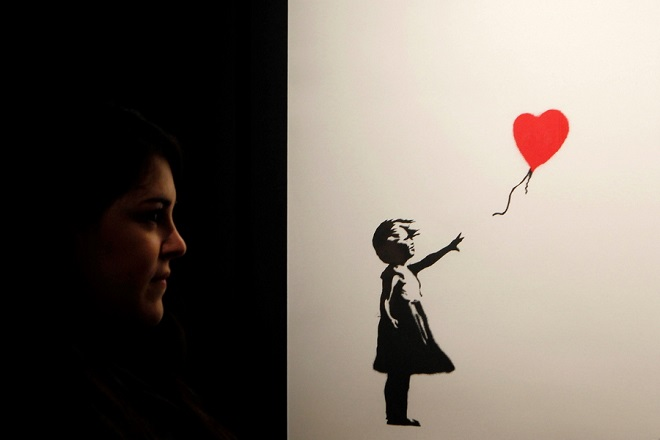 epa07212249 A woman looks at the artwork 'Girl With A Balloon', by British artist Banksy, as she visits the 'unautorized' exhibition 'Banksy, genious or vandal?' during its opening in Madrid, Spain, 06 December 2018. The exhibition, running from 06 December to 10 March, features, for first time in Spain, some 70 artworks by the street artist.  EPA/PAOLO AGUILAR