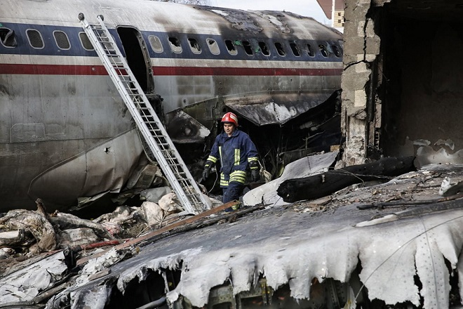 epa07281965 A firefighter walks near the wreckage of a Boeing 707 cargo plane that crashed while landing at Fath airport, near the city of Karaj, Alborz province, Iran, 14 January 2019. According to media reports, at least seven members of the crew have been killed in the accident. One person has reportedly survived, media added.  EPA/HASSAN SHIRAVANI