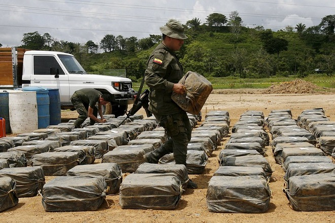 epa01746750 A member of the Colombian Police carries part of the 3,5 tons of Cocaine seized in Necocli, Antioquia department, Colombia, 30 May 2009, during an operation against 'Don Mario' drug cartel. The drug was found hidden in the beaches of that town by Police Commands and was supposed to send to the USA through Panama, Honduras and Mexico.  EPA/LEONARDO MUNOZ