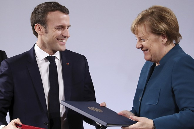 epaselect epa07308791 German Chancellor Angela Merkel (R) and French President Emmanuel Macron  react during the signing of a new France-German friendship treaty in Aachen, Germany, 22 January 2019. President Macron and Chancellor Merkel sign a new friendship treaty, intended to supplement the 1963 Elysee Treaty, pledging to provide deeper economic and defense ties and commitment to the EU.  EPA/FRIEDEMANN VOGEL