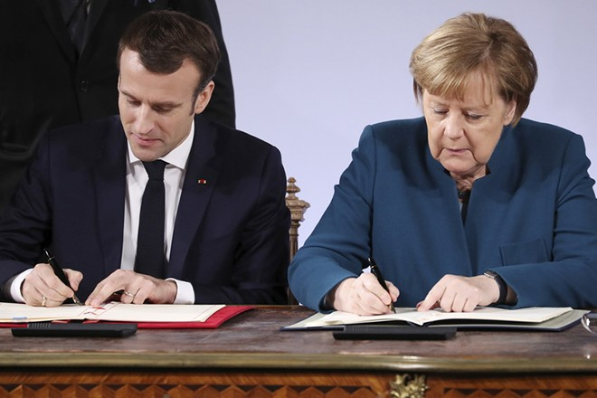 epa07308787 German Chancellor Angela Merkel (R) and French President Emmanuel Macron sign a new France-German friendship treaty in Aachen, Germany, 22 January 2019. President Macron and Chancellor Merkel sign a new friendship treaty, intended to supplement the 1963 Elysee Treaty, pledging to provide deeper economic and defense ties and commitment to the EU.  EPA/FRIEDEMANN VOGEL