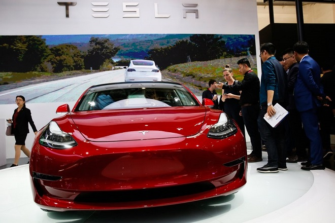 epa06691848 Visitors look at Tesla Model 3 car during Auto China 2018 motor show in Beijing, China, 25 April 2018. The 15th Beijing International Automotive exhibition or Auto China 2018 runs from 25 April to 04 May 2018.  EPA/ROMAN PILIPEY