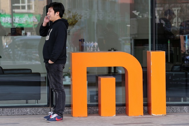 epa06849544 (FILE) - A man uses his mobilephone next to a logo of Chinese mobile phone product manufacturer Xiaomi at Xiaomi's headquarters in Beijing, China, 12 February 2015 (re-issued 29 June 2018). Reports on 29 June 2018 state Chinese mobile phone maker Xiaomi raised an estimated 4.72 billion USD in its IPO in Hong Kong, indicating it will be valued at some 53.9 billion USD. Xiaomi's original target was to be valued at around 100 billion USD.  EPA/WU HONG