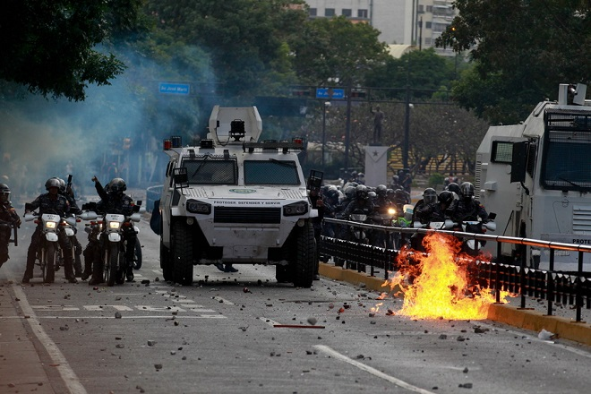 epa07313769 Members of the Bolivarian National Police clash with protesters during a demonstration against the Government of the Venezuela and President Nicolas Maduro in Caracas, Venezuela, 23 January 2019. Thousands of Venezuelans have demonstrated today in the 23 states of the country, against Nicolas Maduro, after the opposition called for people to ignore the legitimacy of the second term of Nicolas Maduro, which has just begun.  EPA/CRISTIAN HERNANDEZ
