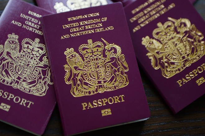 epa04253141 British passports in London, Britain, 13 June 2014. The Home Office has said on 12 July that to help clear the huge backlog of passport applications it will scrap charges for urgent renewals. Some 30,000 people have been impacted by the delays.  EPA/ANDY RAIN