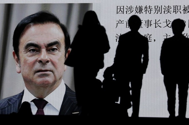 epa07285345 (FILE) - Pedestrians watch large-scale screen displaying a news program reporting on former Nissan Motor Co Ltd chairman Carlos Ghosn attending a court hearing at Tokyo district court, in Tokyo, Japan, 08 January 2019 (reissued 15 January 2019). According to media reports on 15 January 2019, a Tokyo court rejected a release on bail request of former Nissan CEO Carlos Ghosn. The former Nissan and Renault chairman is accused by Japanese authorities of under-reporting his income.  EPA/KIMIMASA MAYAMA
