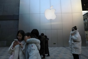 epa07305376 Shoppers look at their mobile phones in front of an Apple store in shopping mall in Beijing, China, 21 January 2019. China's gross domestic product (GDP) grew 6.6 percent in 2018, according to a report of the National Bureau of Statistics issued on 21 January 2019.  EPA/HOW HWEE YOUNG