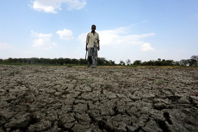 epa05303992 An Indian villager walks in a part of the dried up bed of Upper Lake at Bishankhedi village, Bhopal, India, 13 May 2016. Many Indian states have been affected by drought and have been hit hard by water scarcity.  EPA/SANJEEV GUPTA