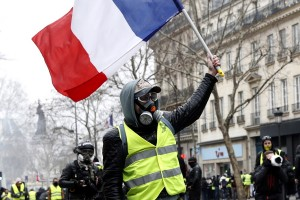 epa07338479 A protester from the 'Gilets Jaunes' (Yellow Vests) waves a French flag  as clashes erupt near the Republic square with the police forces during the 'Act XII' demonstration (the 12th consecutive national protest on a Saturday) dedicated to the victims of the movement in Paris, France, 02 February 2019. The so-called 'gilets jaunes' (yellow vests) is a grassroots protest movement with supporters from a wide span of the political spectrum, that originally started with protest across the nation in late 2018 against high fuel prices. The movement in the meantime also protests the French government's tax reforms, the increasing costs of living and some even call for the resignation of French President Emmanuel Macron.  EPA/YOAN VALAT
