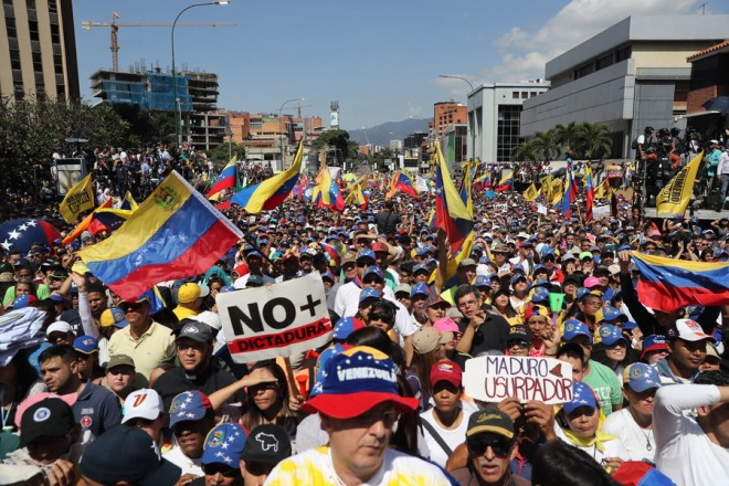 epa07339185 Sympathizers of the opposition wave the Venezuelan flags and hold signs during a march against Nicolas Maduro's Government, in Caracas, Venezuela, 02 February 2019. Maduro and his opponent National Assembly leader Juan Guaido have called on their supporters to take to the streets as international pressure increased on Maduro to resign. Guiado had declared himself interim president of Venezuela on 23 January and promised to guide the country toward new election as he consider last May's election not valid.  EPA/LEONARDO MUNOZ