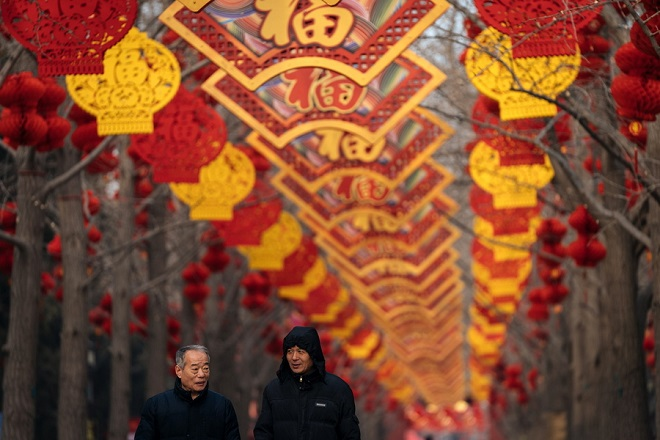 epa07329108 Chinese men walk next to red lanterns hanging from trees to celebrate the upcoming Chinese Lunar New Year, at Ditan Park, in Beijing, China, 29 January 2019. The Chinese Lunar New Year, or Spring Festival, which falls on 05 February this year, will mark the Year of the Pig.  EPA/ROMAN PILIPEY