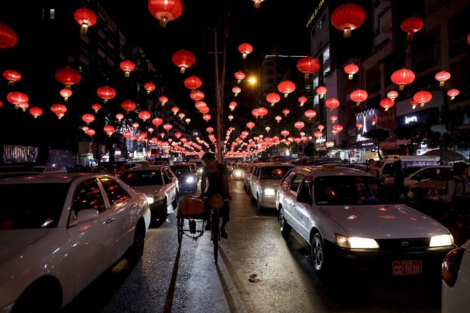 epaselect epa07334041 A man drives a trishaw along a road decorated with lit red lanterns in celebrations for the upcoming Chinese Lunar New Year or Spring Festival at busy Chinatown in Yangon, Myanmar, 31 January 2019. The Chinese New Year, the Year of the Pig, begins on 05 February 2019 and ends on 24 January 2020.  EPA/LYNN BO BO