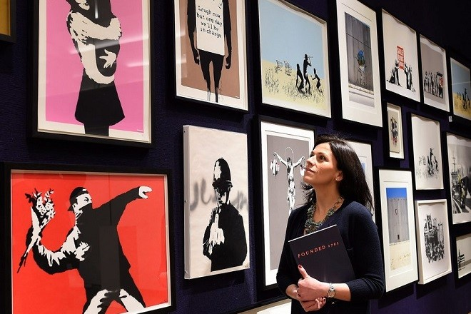 epa04578528 A Bonham's auction house staff looks at artworks by British graffiti artist Bansky displayed during a media preview at Bonhams in London, Britain, 23 January 2015. A collection of 30 Banksy prints owned by the British gallery owner, Steve Lazarides, formerly the agent of the celebrated graffiti artist, are to be auctioned at the Contemporary Art & Design sales 'Founded 1793' on 28 January 2015.  EPA/ANDY RAIN