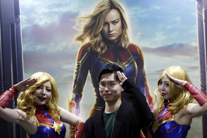 epa07203254 A visitor strikes a pose with booth attendants in front of a poster of the upcoming Captain Marvel movie during the Tokyo Comic Con 2018 at Makuhari Messe in Chiba, east of Tokyo, Japan, 02 December 2018. The three-day-long event offers comic fans an enthusiastic experience with exhibitions and displays of Japanese and American pop culture. Some 50,000 visitors were expected for this year's edition.  EPA/FRANCK ROBICHON
