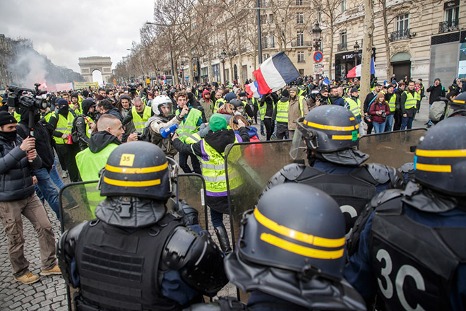 epa07355294 Protesters from the 'Gilets Jaunes' (Yellow Vests) movement face the police forces on the Champs Elysees during the 'Act XIII' demonstration (the 13th consecutive national protest on a Saturday) in Paris, France, 09 February 2019. The so-called 'Gilets Jaunes' is a grassroots protest movement with supporters from a wide span of the political spectrum, that originally started with protest across the nation in late 2018 against high fuel prices. The movement in the meantime also protests the French government's tax reforms, the increasing costs of living and some even call for the resignation of French President Emmanuel Macron.  EPA/CHRISTOPHE PETIT TESSON