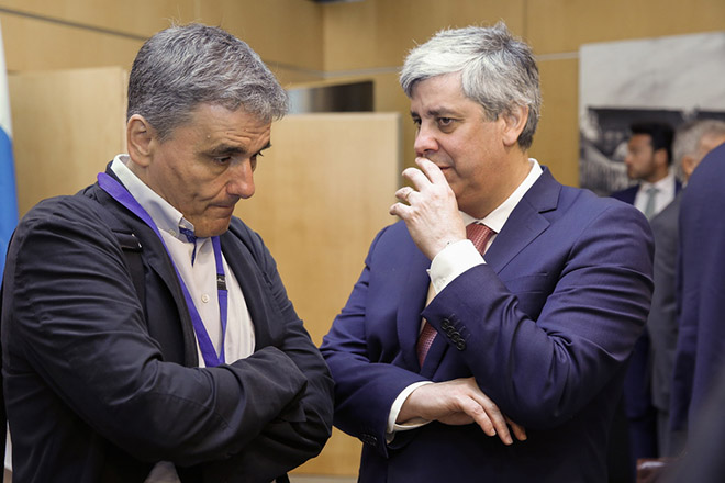 epa06827090 Greek Finance Minister Euclid Tsakalotos (L) and The President of the Eurogroup, Portuguese Finance Minister Mario Centeno (R), during a meeting for the 20th anniversary of Eurogroup at Castle of Senningen in Luxembourg, 21 June 2018. The Eurogroup will assess the progress achieved by Greece in implementing the prior actions required under the fourth (and the final) review of its programme.  EPA/JULIEN WARNAND