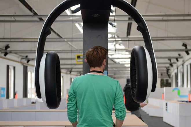 epa03850771 A man stands between giant sets of headphones listening to music at the Postbahnhof venue in Berlin, Germany, 4 September 2013. The Berlin Music Week takes place from 4 September to 8 September 2013 and features conferences, speeches, concerts and parties in its program.  EPA/BRITTA PEDERSEN