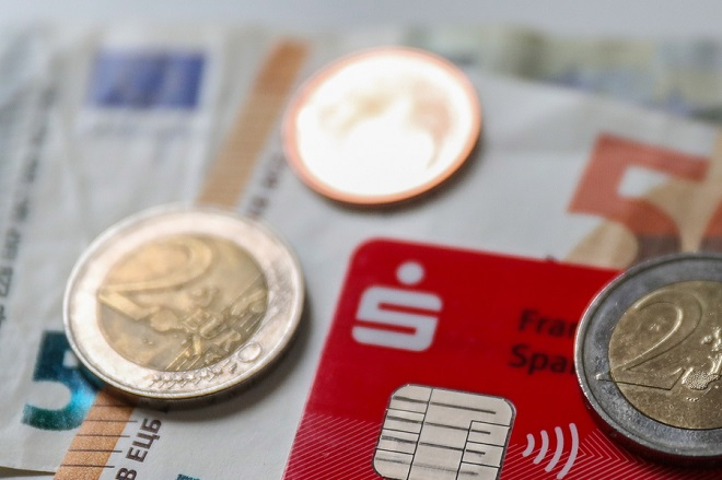 epa07363630 Some banknotes and coins are seen together with a credit card with an integrated NFC technology chip for cash-less payment in a shop in Frankfurt am Main, Germany, 12 February 2019. Later on 12 February the German Federal Bank 'Bundesbank' will present the results of a study 'on Costs of cash payments in retail trade'.  EPA/ARMANDO BABANI