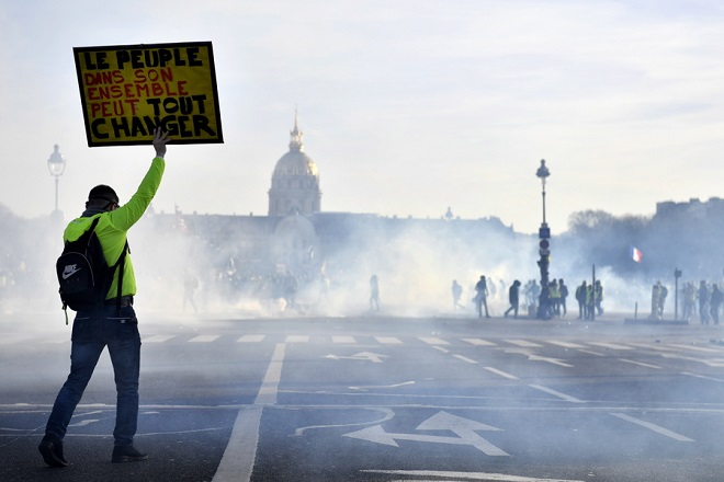 epaselect epa07375227 A protester from the 'Gilets Jaunes' (Yellow Vests) movement holds a sig reading 'People as a whole can change everything' during clashes with French riot Police near the Invalides during the 'Act XIV' demonstration (the 14th consecutive national protest on a Saturday) in Paris, France, 16 February 2019. The so-called 'Gilets Jaunes' is a grassroots protest movement with supporters from a wide span of the political spectrum, that originally started with protest across the nation in late 2018 against high fuel prices.  EPA/JULIEN DE ROSA