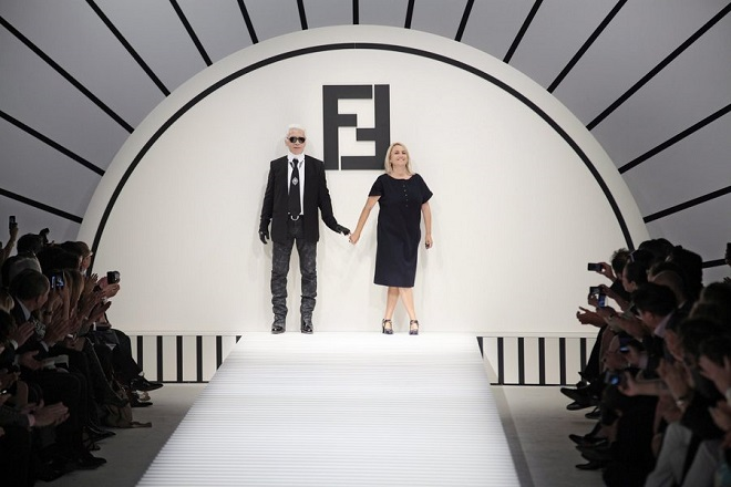 epa02929186 German designer Karl Lagerfeld (L) and Italian designer Silvia Fendi (R) appear on the catwalk after the presentation the Fendi collection at the Milan Fashion Week Ready-to-wear Spring-Summer 2012, in Milan, Italy, 22 September 2011. The fashion week runs from 21 to 27 September.  EPA/GIULIO DI MAURO