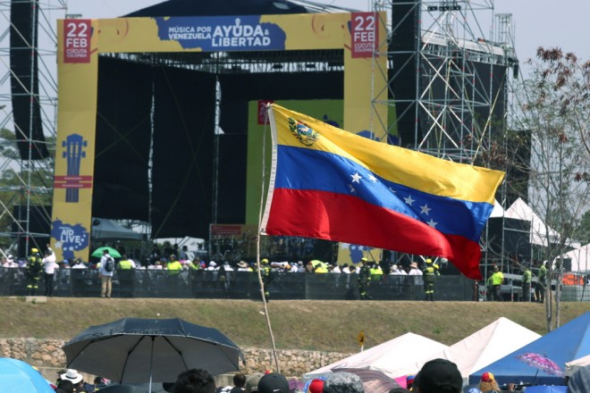 epa07388339 A Venezuelan flag flies in front of the Venezuela Aid Live concert stage at the Tienditas border bridge, in Cucuta, Colombia, 22 February 2019. The concert 'Venezuela Aid Live', which was called by the billionaire Richard Branson, began on the Colombian side of the Tienditas border bridge with the national anthem of Colombia and the applause of the thousands of people who attended the event. The call, which was answered by 32 artists from a dozen countries, aims to promote humanitarian aid to support Venezuelans affected by the crisis in their country and raise 100 million dollars for the needy.  EPA/MAURICIO DUENAS CASTANEDA