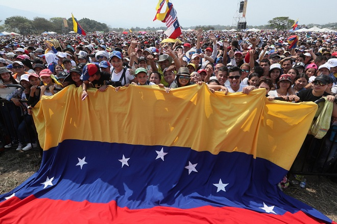 epa07388344 A group of people hold a large Venezuelan flag during the Venezuela Aid Live concert at the Tienditas border bridge, in Cucuta, Colombia, 22 February 2019. The concert 'Venezuela Aid Live', which was organised by the British billionaire Richard Branson, began on the Colombian side of the Tienditas border bridge with the national anthem of Colombia and the applause of the thousands of people who attended the event. The event, which was attended by 32 artists from a dozen countries, aims to promote humanitarian aid to support Venezuelans affected by the crisis in the country and raise 100 million US dollars for the needy.  EPA/MAURICIO DUENAS CASTANEDA