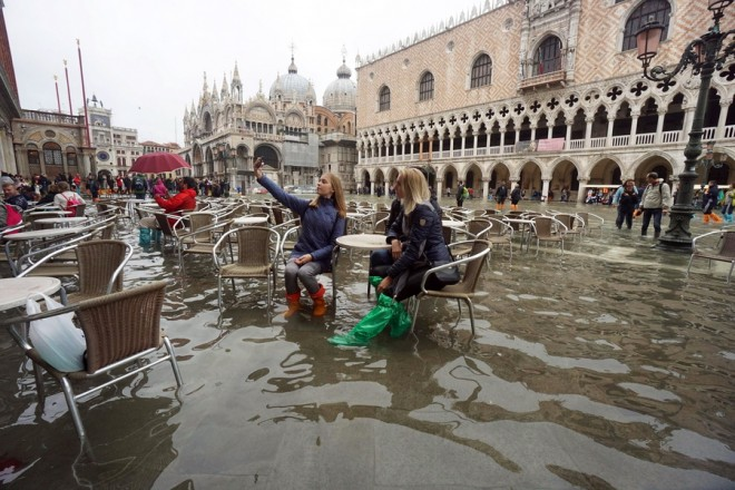 epa07135183 Tourists pose for a selfie picture in high water at the San Marco Square in Venice, northern Italy, 01 November 2018. The tide reached some 120 centimeters above the sea level.  EPA/ANDREA MEROLA