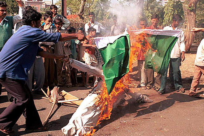 BPL01 - 20011226 - BHOPAL, INDIA : Indian shanty-dwellers aligned with the Bharatiya Janata Party (BJP) tear apart a burning Pakistani flag during an anti-Pakistan protest in Bhopal 26 December 2001. The demonstrators called for a full scale war with Pakistan following a daring terrorist attack on India's national parliament, allegedly engineered by terrorists operating from Pakistan. EPA PHOTO AFP/STR/jd/tc