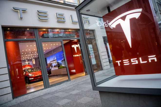 epa07406756 A person walks past a Tesla showroom in Berlin, Germany, 01 March 2019. Shares of US electric car maker Tesla fell a day after store closures and job cuts were announced.  EPA/JENS SCHLUETER
