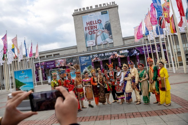 epa07414560 Women and men wearing traditional costumes from Malaysia pose for a photo in the front of the entrance to the International Travel Trade Show (ITB), in Berlin, Germany, 05 March 2019. Around 10,000 companies from 181 countries and regions are presenting their new offers in the travel industry from 06 to 10 March 2019. Malaysia is partner country of the fair this year.  EPA/JENS SCHLUETER