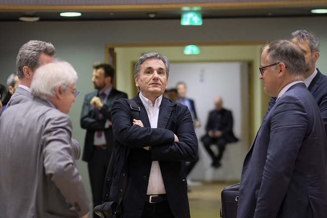 epa07429024 Greek Finance Minister Euclid Tsakalotos (C) stands together with participants prior to the Eurogroup Finance Ministers' meeting in Brussels, Belgium, 11 March 2019. According to the agenda of the European Commission the Eurogroup will be informed on the main findings of the 2nd enhanced surveillance mission to Greece and will discuss the housing markets in the eurozone. Others are not identified.  EPA/OLIVIER HOSLET
