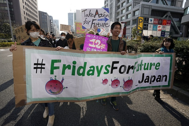 epa07438430 People march to demand actions on climate change in Tokyo, Japan, 15 March 2019. A hundred people gathered and marched in Tokyo to rise awarness on climate change. Hundreds of thousands of students are expected to strike worldwide demanding urgent political action on climate change.  EPA/FRANCK ROBICHON