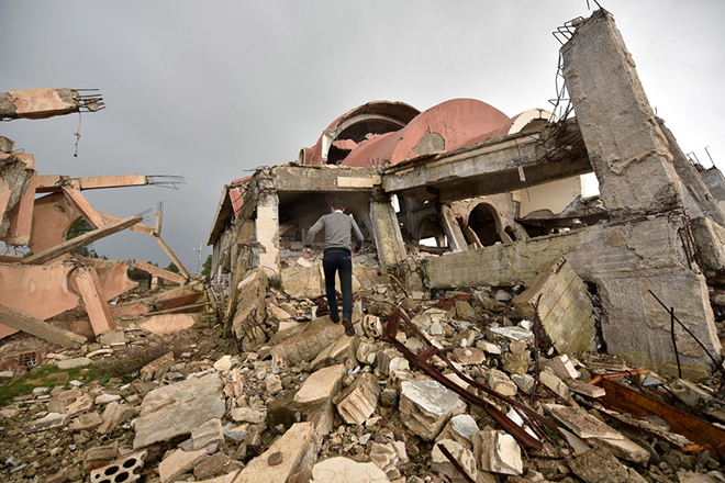 epa07389087 A Syrian man inspects the ruins of Tal Nasri church in the Assyrian-majority Khabur valley northwest of al-Hasakah, north of Syria, 22 February 2019. Tal Nasri church is one of christians churchs which was destroyed by Islamic state (IS) fighters during their control over the regions of northern Syria.  EPA/MURTAJA LATEEF